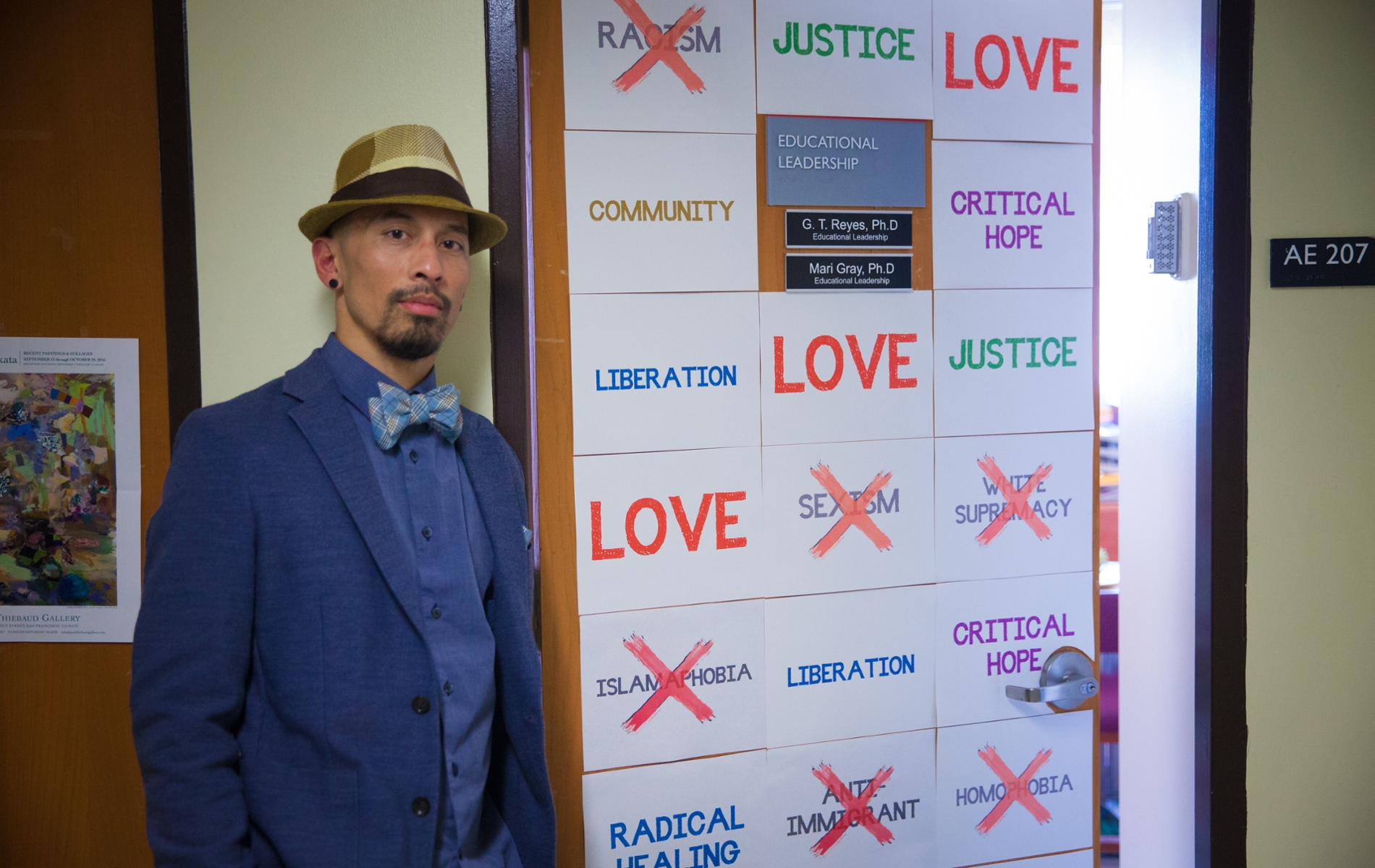 "A professor in a coat and fedora stands in front of an office door with pieces of paper with words making a ""quilt"""