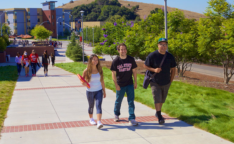 A group of students walk on campus with the dorms in the background