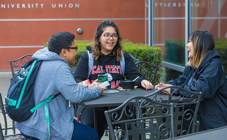 Three students laugh and chat at a table outside the new university union.