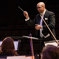 A conductor directs the orchestra